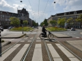 So many modes of transportation in Amsterdam! This roundabout has: a bike path, a sidewalk, a vehicle road and rail going through the middle.