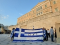 """Everyone was getting kicked off the front steps of parliament except these people with their big Greek flag with """"no"""" written on it."""