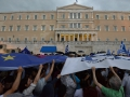 """It started raining during the """"yes"""" protest and people used their huge flags as umbrellas."""