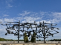 A monument for those at Dachau and the baracks behind.