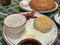 Glorious southern breakfast with biscuits and gravy, eggs, and an apple filled pancake!